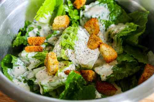 homemade caesar salad dressing on lettuce with croutons