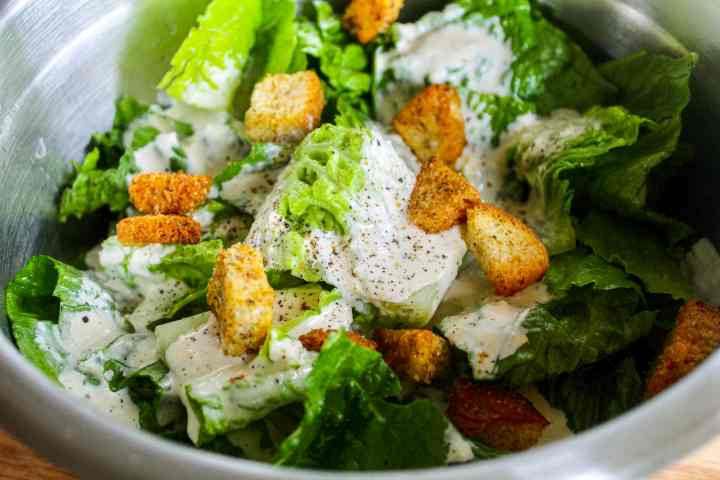 caesar salad dressing on lettuce with croutons