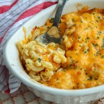 baked mac and cheese in a white dish with a silver spoon