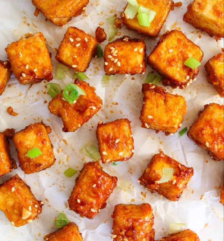 spicy honey garlic tofu on a white background with a green onion garnish