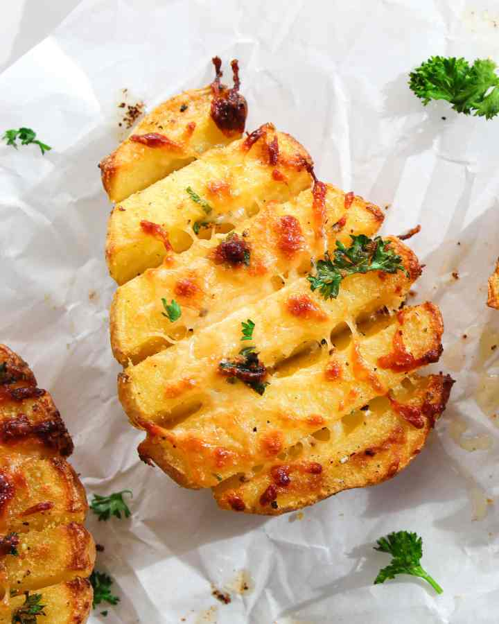 easy scored baked potatoes topped with herbs and cheese