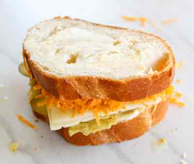 a dill pickle grilled cheese sandwich on a white background