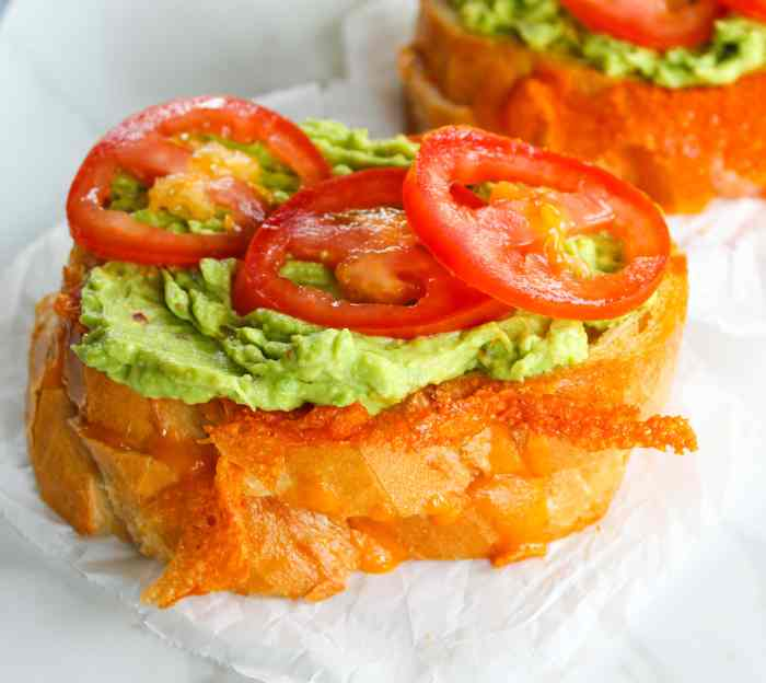 Tomato and avocado on a grilled cheese sandwich.