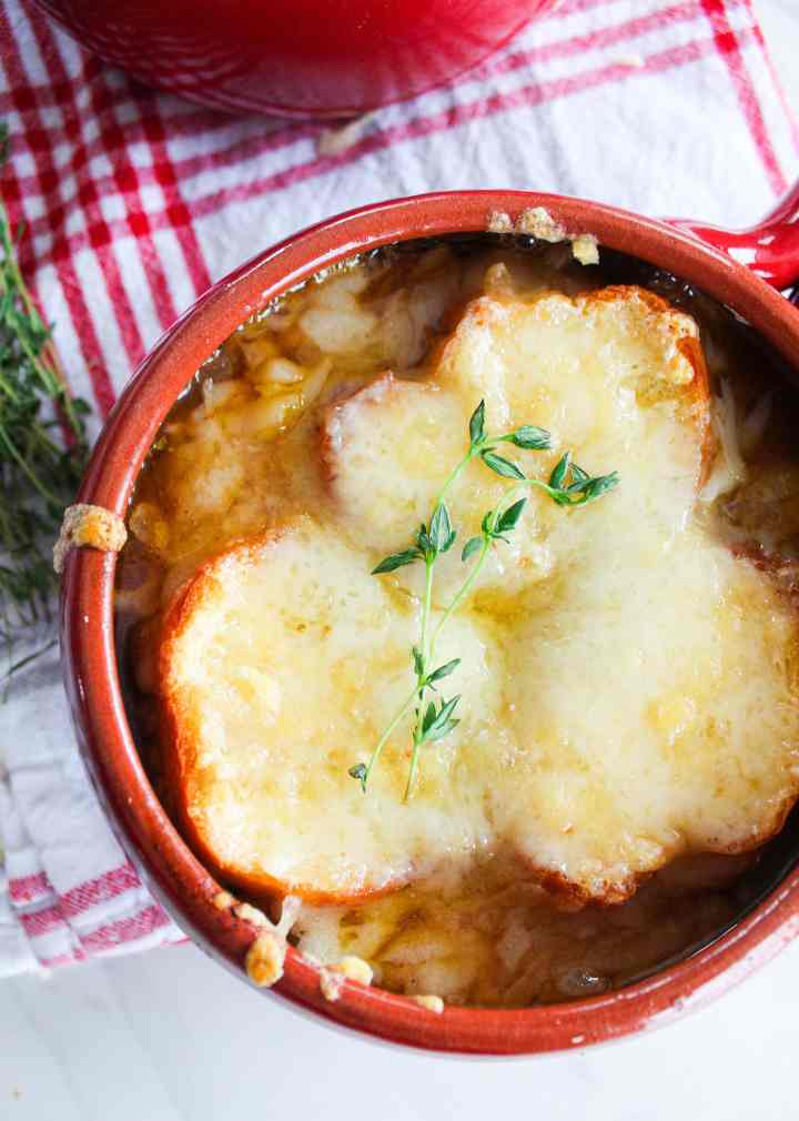 vegetarian French onion soup in a red bowl