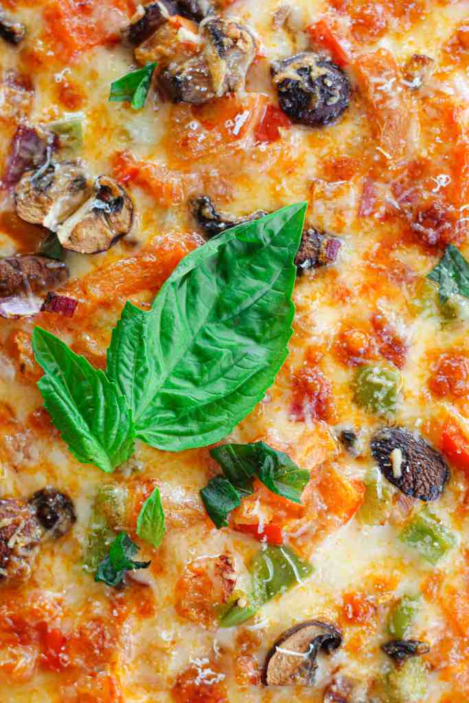 close up of sheet pan pizza topped with basil