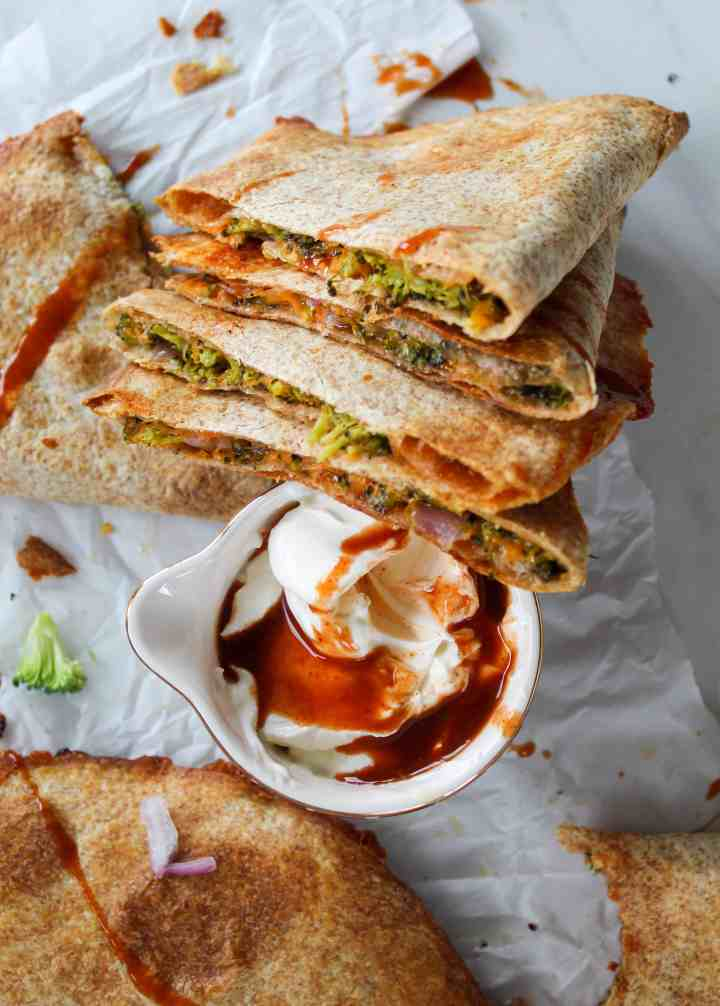 broccoli cheddar quesadillas cut into thirds with dipping sauce