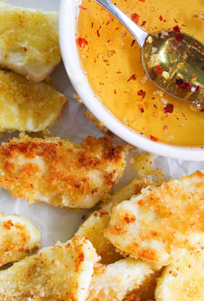 pan fried halloumi with a white dish filled with honey and red pepper flakes