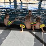 Kinder strampeln beim Sitzen im Wasser.