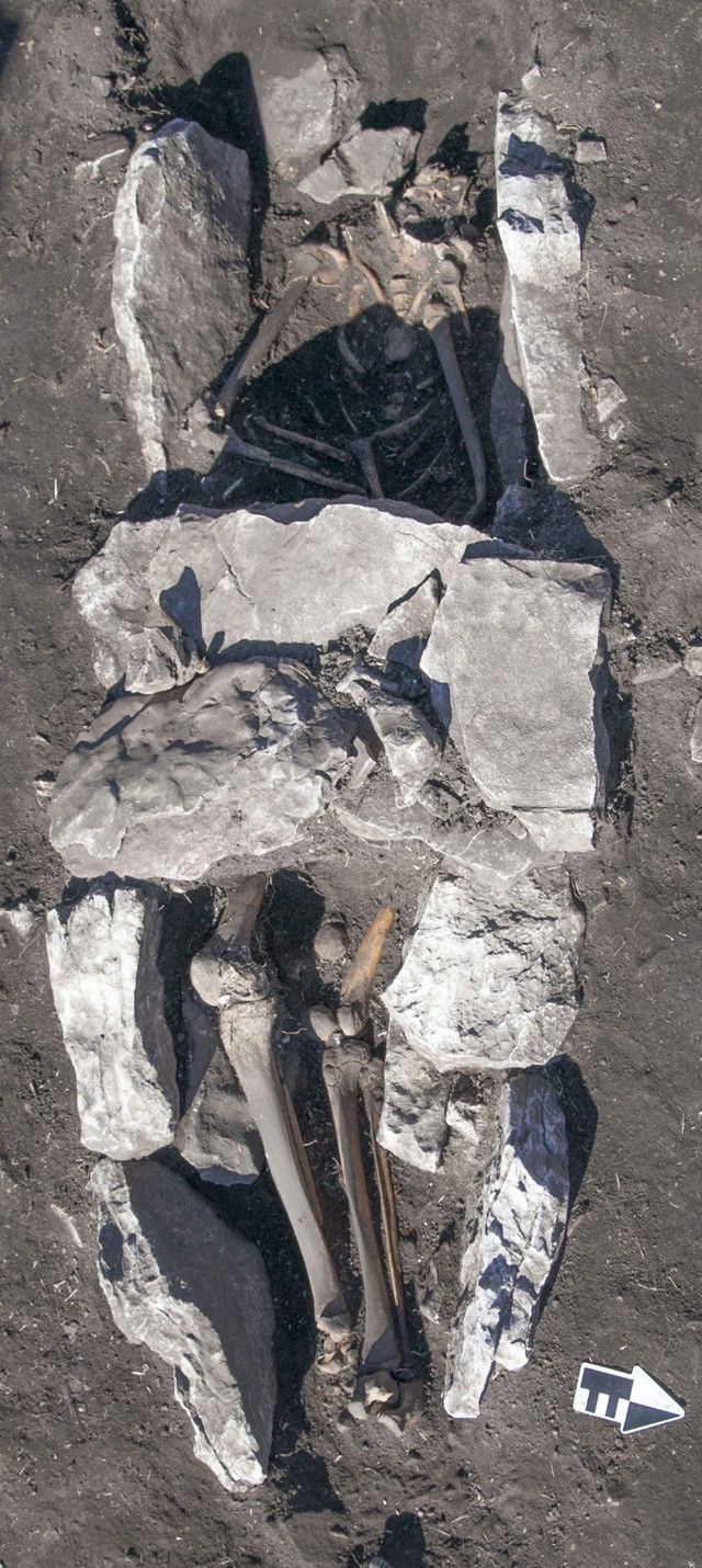 Ανθρώπινη ταφή στο μέσο του βωμού τέφρας με τις καλυπτήριες πλάκες στην περιοχή της λεκάνης