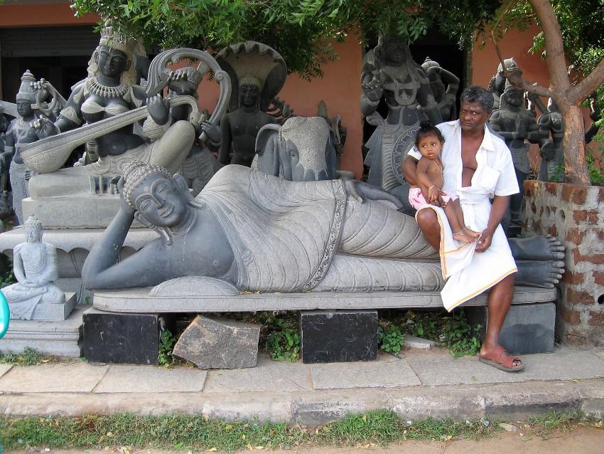 Mamallapuram Monsieur tenant un bébé, assis sur une sculpture de granit noir