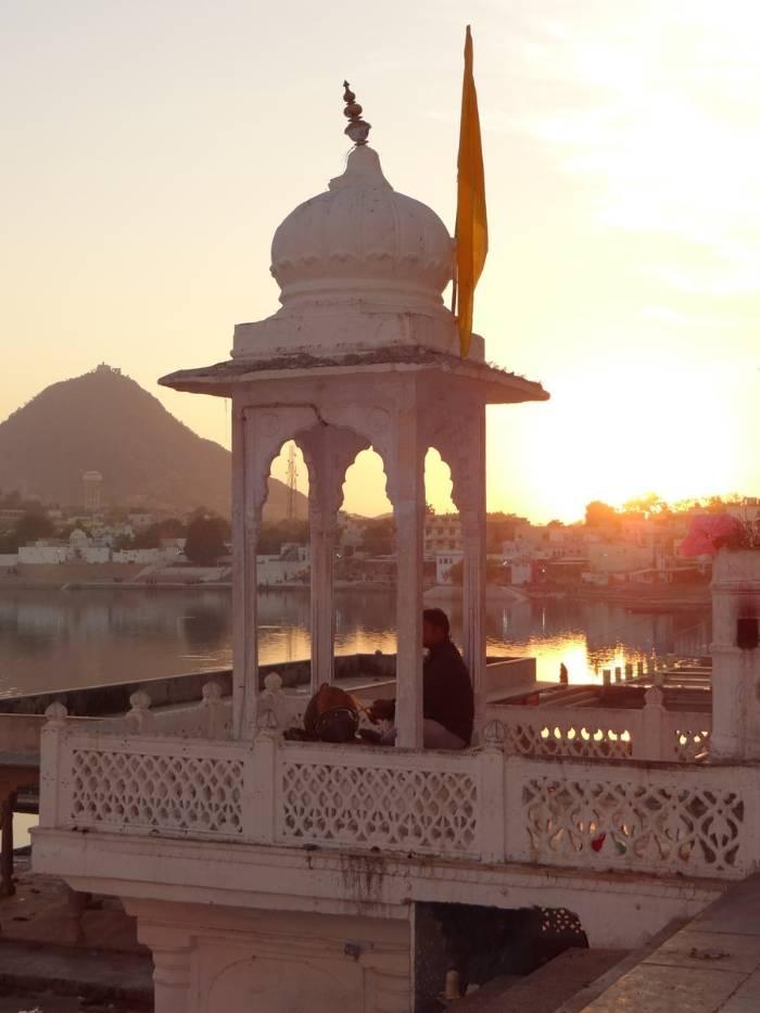 Tourelle blanche sir coucher de soleil avec un homme assis