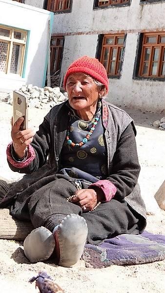 Ladakh Grand-Mère assise par terre avec 1 téléphone portable
