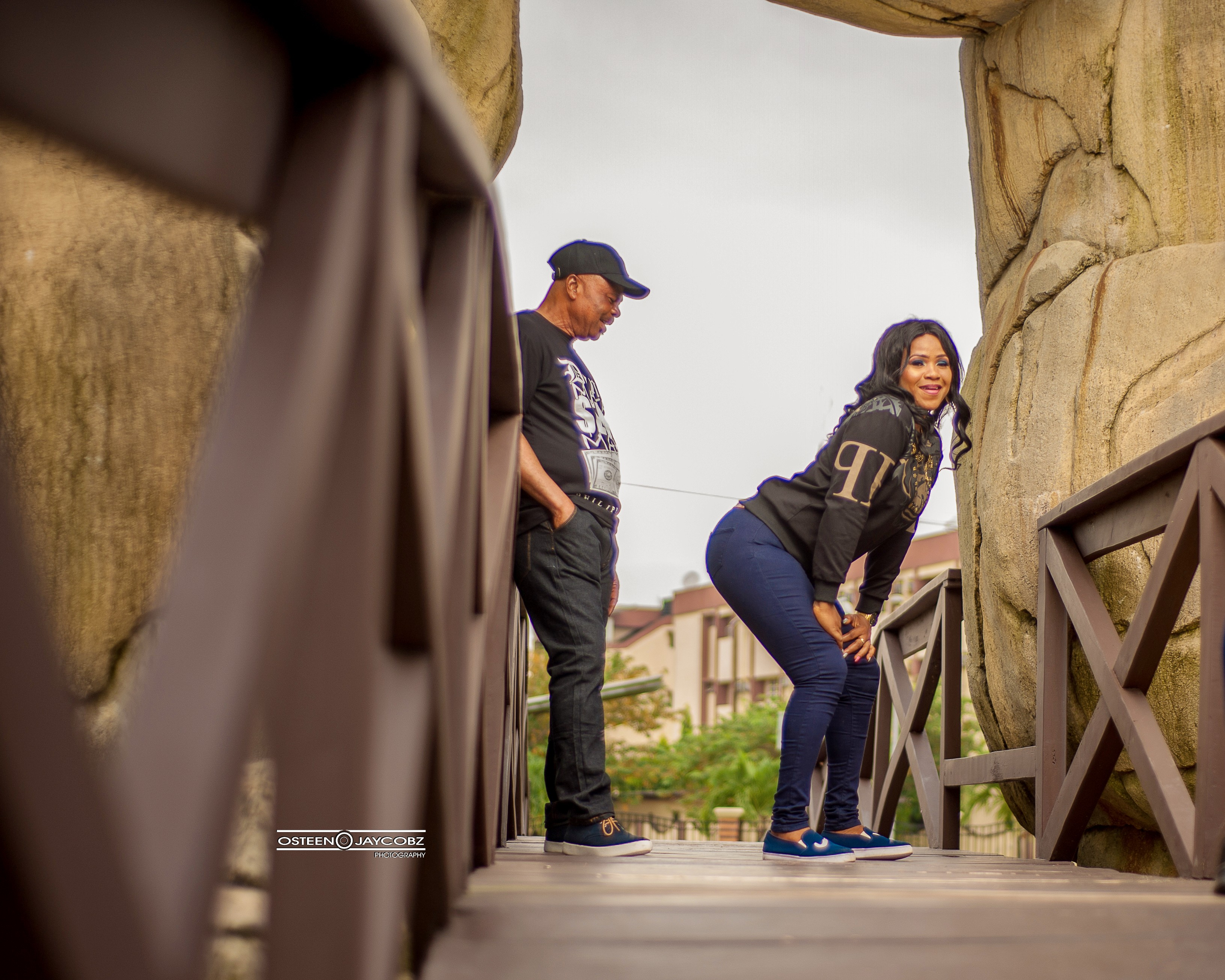 Elderly man stares at his partner's backside in their pre-wedding photos