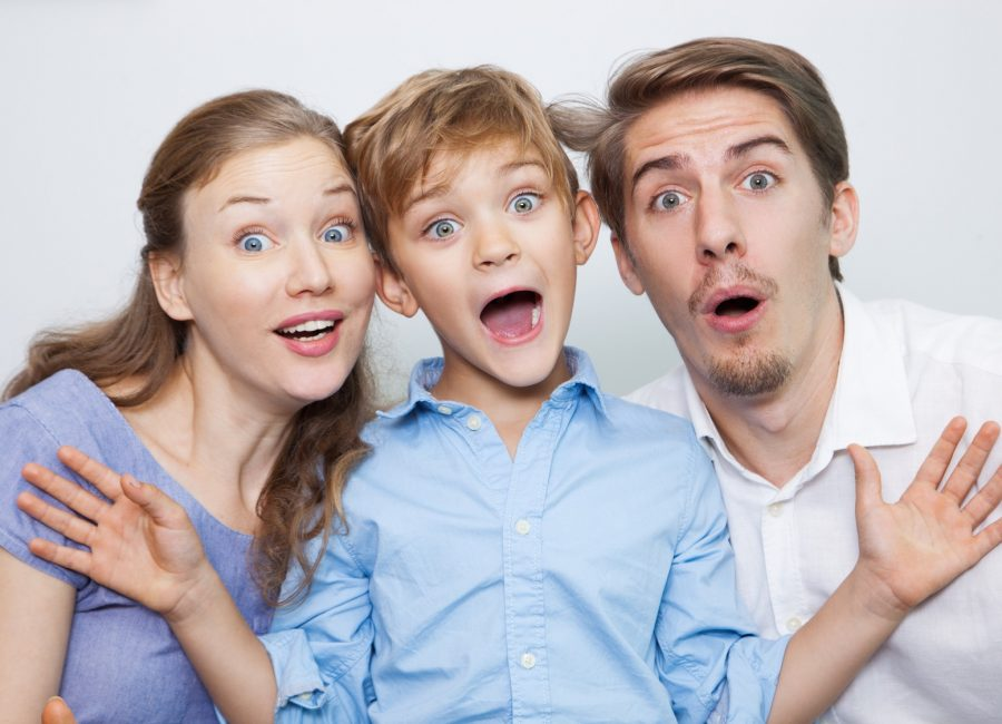 Portrait of astonished young Caucasian family with little son looking at camera with open mouth. Boy outstretching arms