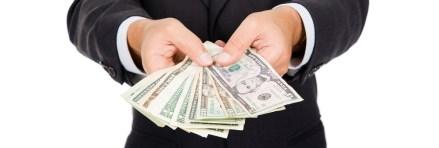 a man holding a dollar bill upfront