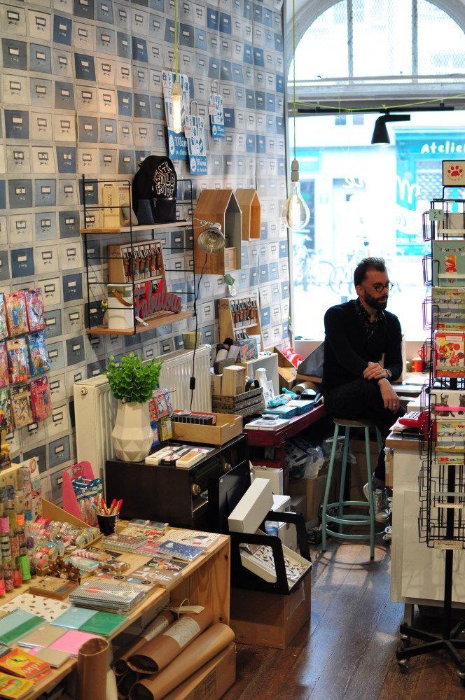 Nikosan derrière le comptoir de la jolie boutique