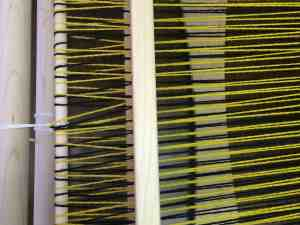 See how the strands behind the heddle are crossing over each other rather than going straight through each slot or eye?