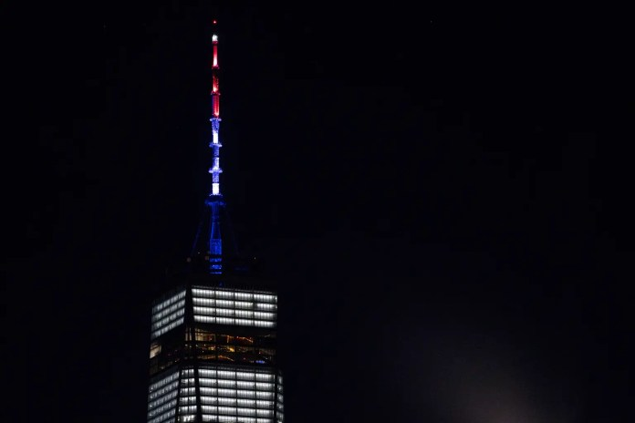 As ordered by New York Gov. Andrew Cuomo, the spire of One World Trade Center is illuminated in red, white and blue following a deadly rampage down a bike path not far from the building Tuesday, Oct. 31, 2017, in New York. A motorist in a rented Home Depot truck drove onto a bike path, striking and killing several people. (AP Photo/Craig Ruttle)