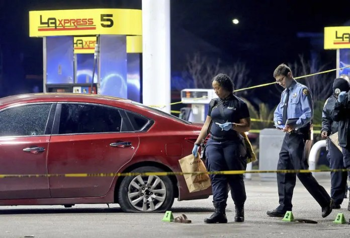 Crime scene technicians gather evidence next to a bullet-riddled red Nissan sedan with a homicide victim inside as New Orleans Police investigate after several people were shot, in the lower Ninth Ward of New Orleans on Mardi Gras night, Tuesday, Feb. 13, 2018. (Michael DeMocker/NOLA.com The Times-Picayune via AP)