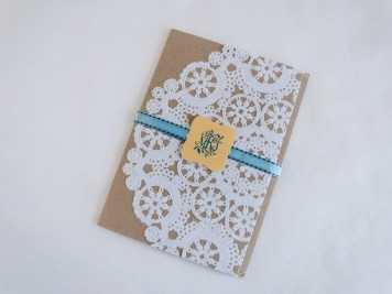 A paper doily glued to the enclosure offsets by a ribbon and monogram that (literally) tie everything together.