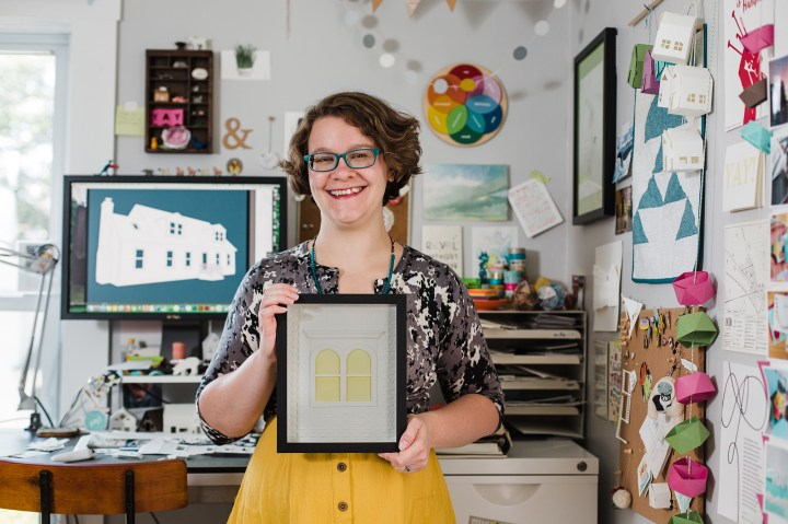 Abigail McMurray, yeiou paper objects, standing in workspace holding finished framed paper sculpture
