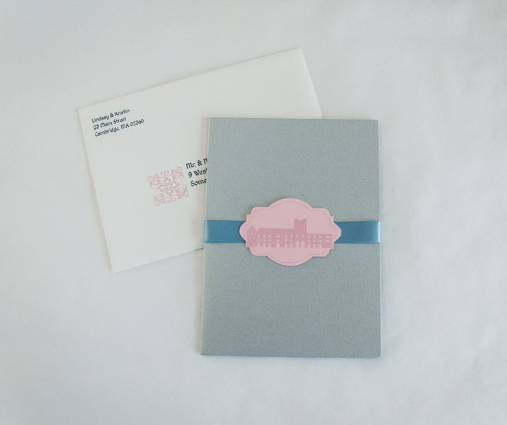 Custom printed envelopes introduce the pink and blue theme.