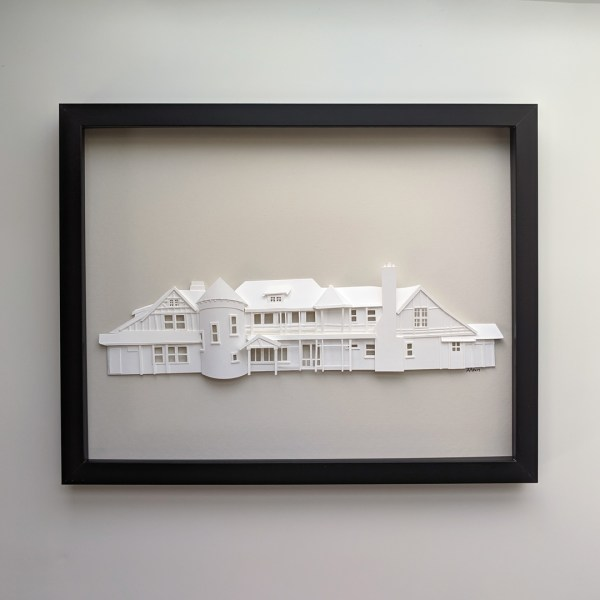 Low-relief paper sculpture of family vacation home made of white paper on a light gray background in a black frame