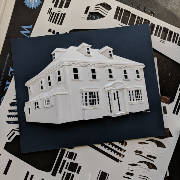 Paper house portrait with navy blue background on top of scraps from the design process.