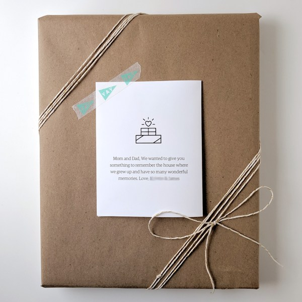 Finished house portrait wrapped with brown kraft paper and baker's twine with gift note on top