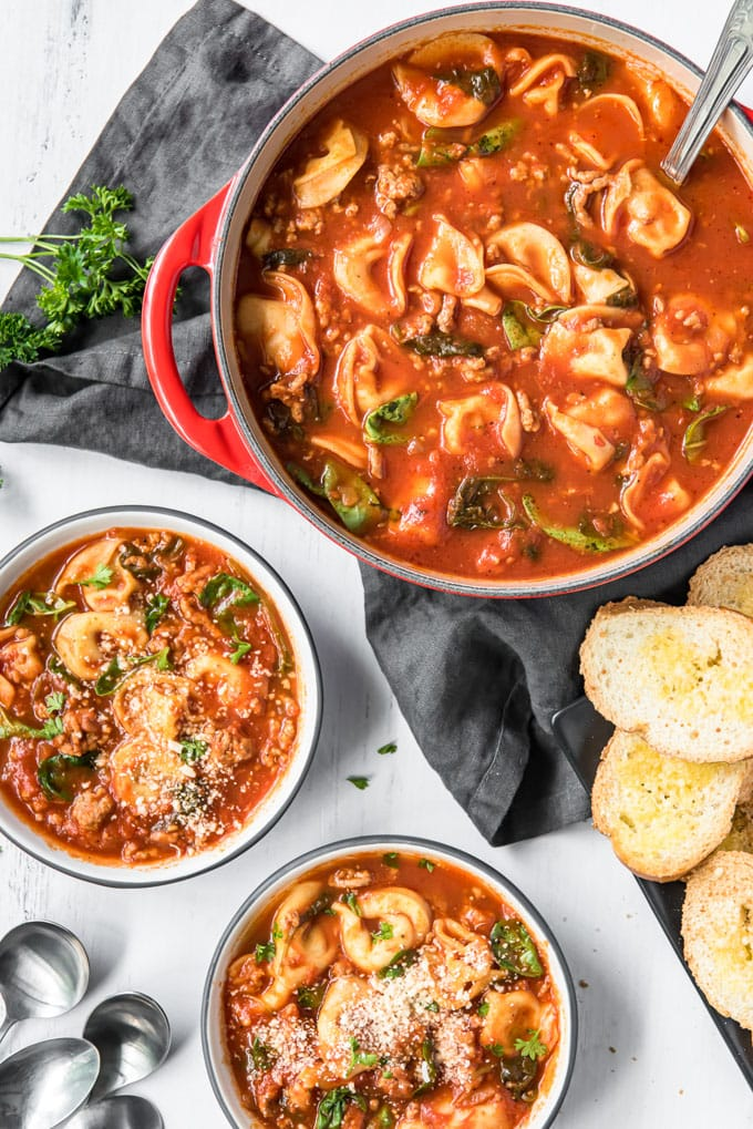 An overhead image of a pot of tortellini soup plus two serving bowls also full of soup