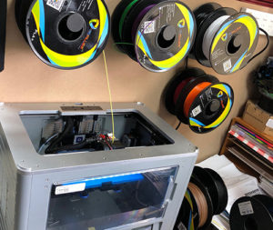Photo of a 3D printer and reels of filament