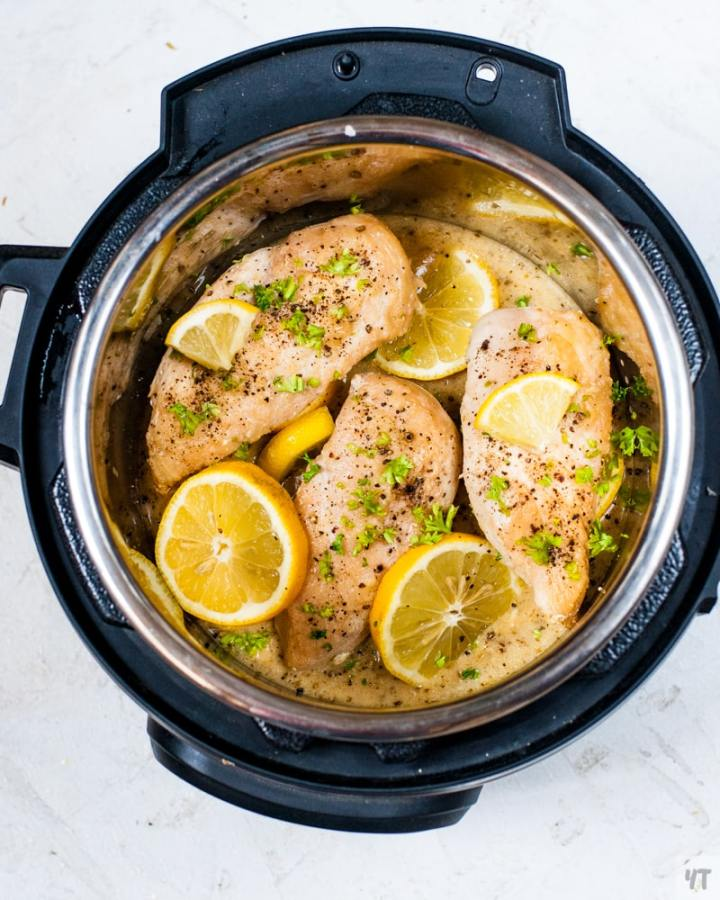 instant pot lemon garlic chicken inside the inner pot with a garnish of lemon slices and parsley