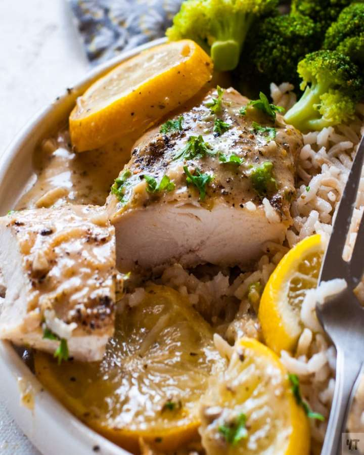 Close up of instant pot lemon garlic chicken on a white plate with a garnish of lemon slices and parsley on a bed of brown rice and steamed brocolli