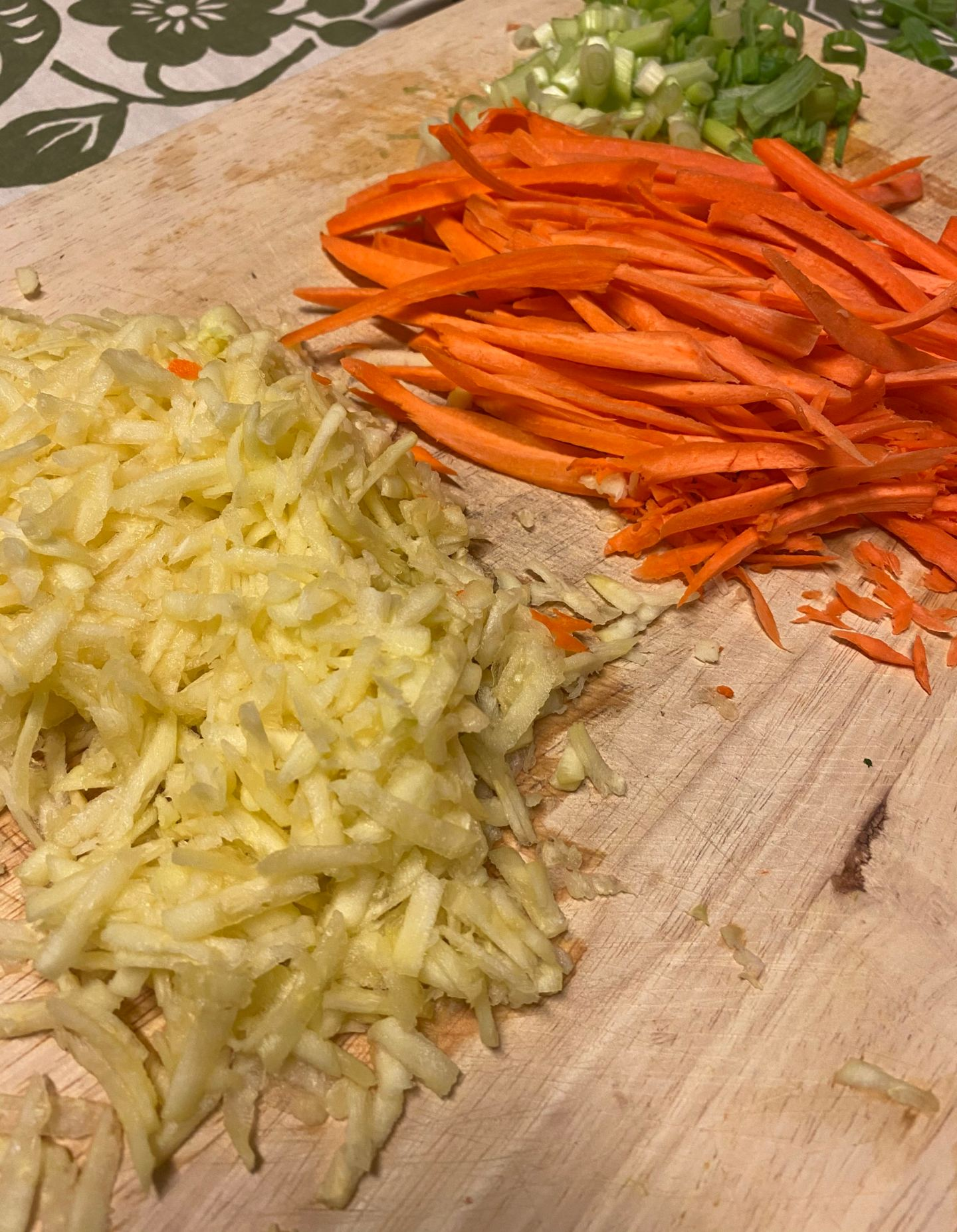 Shredded zucchini, chopped carrots, and scallions on a wooden board.
