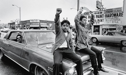 Two young Chicano men ride on the hood of a car and raise their fists during a National Chicano Moratorium Committee march in Los Angeles, California, on August 29, 1970, in opposition to the war in Vietnam.