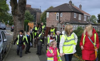 Parents help children walk to school in Salford