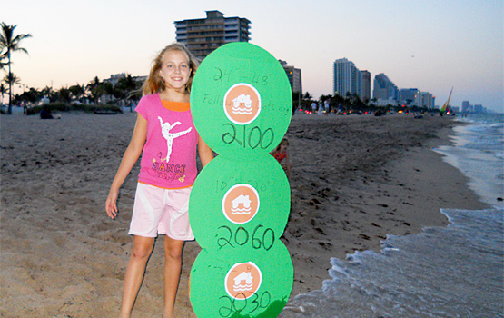 A girl holds sea level markers. Photo by 350.
