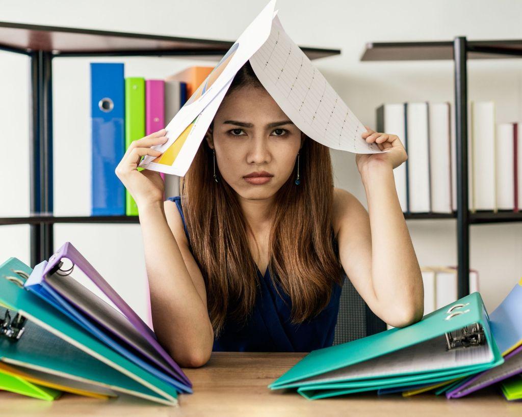 femme devant un bureau qui met un livre sur sa tête parce qu'elle st angoissée