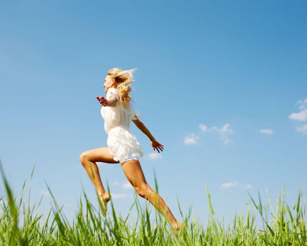 Femme qui saute dans l'herbe