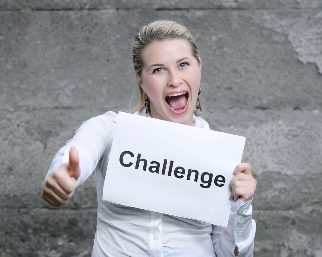 femme qui sourit et qui tient une pancarte challenge