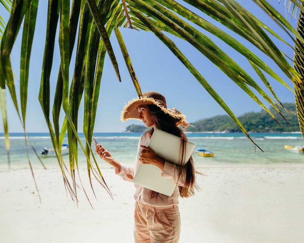 femme avec un telephone dans la main sur une plage sous un cocotier