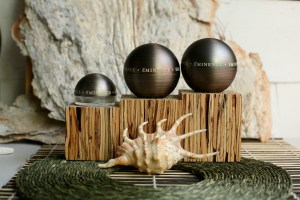 "spherical containers of ""eminence"" cream posed on miniature daises behind a murex shell."