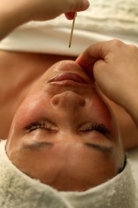 A small, gold-colored pointing tool is about to stimulate a relaxed client's chin in a unique facial massage.
