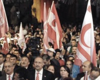 Mehmet Ali Talat'ın seçim kampanyası sırasında, rüşvet ve usulsüzlere adı karışmış o dönemde ÖP başkanı olan sonra UBP'ye dönen Turgay Avcı ile İzcan, TC-KKC bayrakları altında birçok yan yana gelip ayni kürsüyü de paylaşmışlardı
