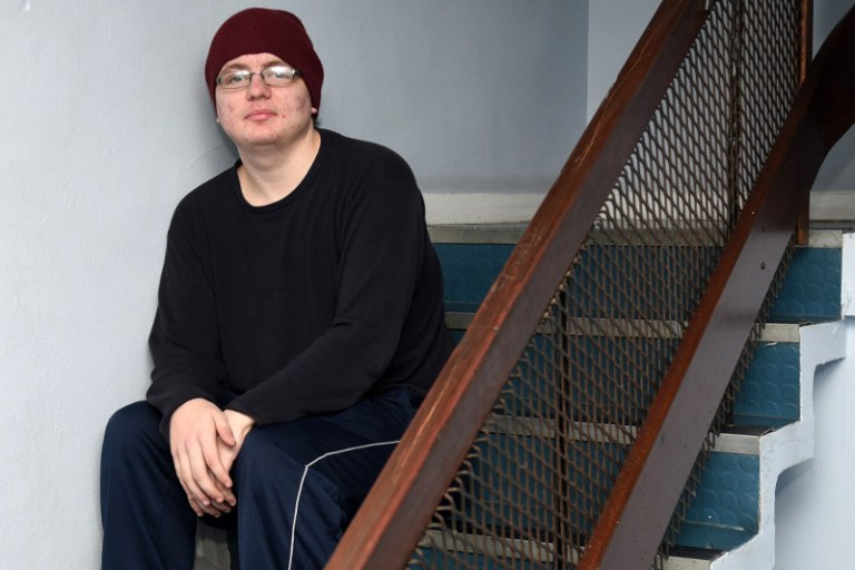 young_man_red_cap_stairs_seated_left_horizontal_2