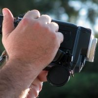 A man's hands holding a camcorder