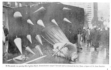 The photo depicts an overturned float of the statue of St. Jean the Baptiste without a head. Riot police can be seen in the background.