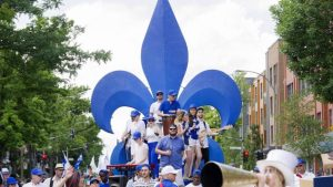 The photo depicts a celebration of the St-Jean-Baptiste Day. The performers are portrayed playing music and singing on top of the moving stage, which is decorated with a big emblem of a blue fleur-de-lis, while the crowd watches them.