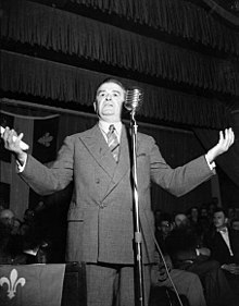 The photo depicts Maurice Duplessis giving a speech during the 1952 election campaign.