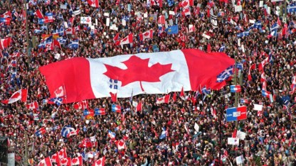The photo depicts a large crowd of people waiving Canadian and Quebec flags (as well as other signs) during the 1995 Referendum. A huge Canadian flag held by a large amount of people can be seen in the middle of the photo.